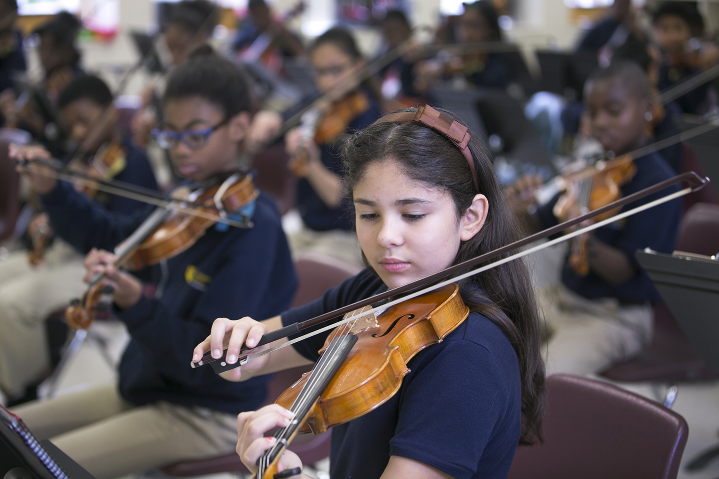 The photo shows a student violin performer.