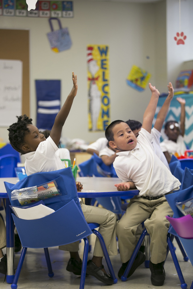 The photo shows primary school students with their arms raised to answer the teacher's question.
