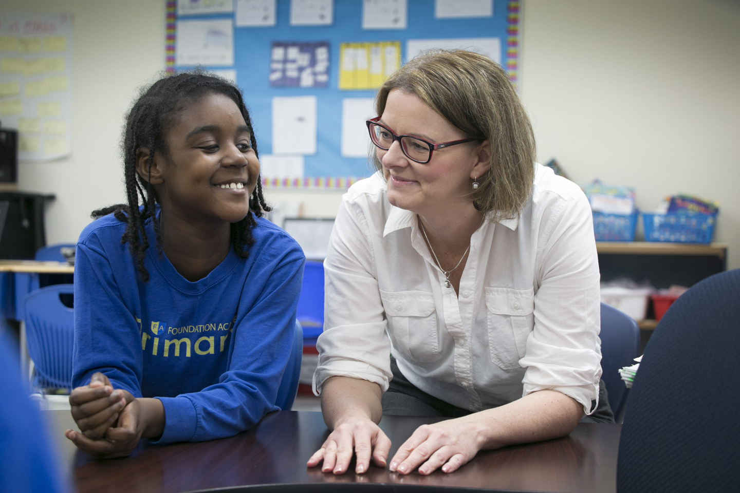 The photo shows a guidance counselor enjoying a happy moment with a primary school student.