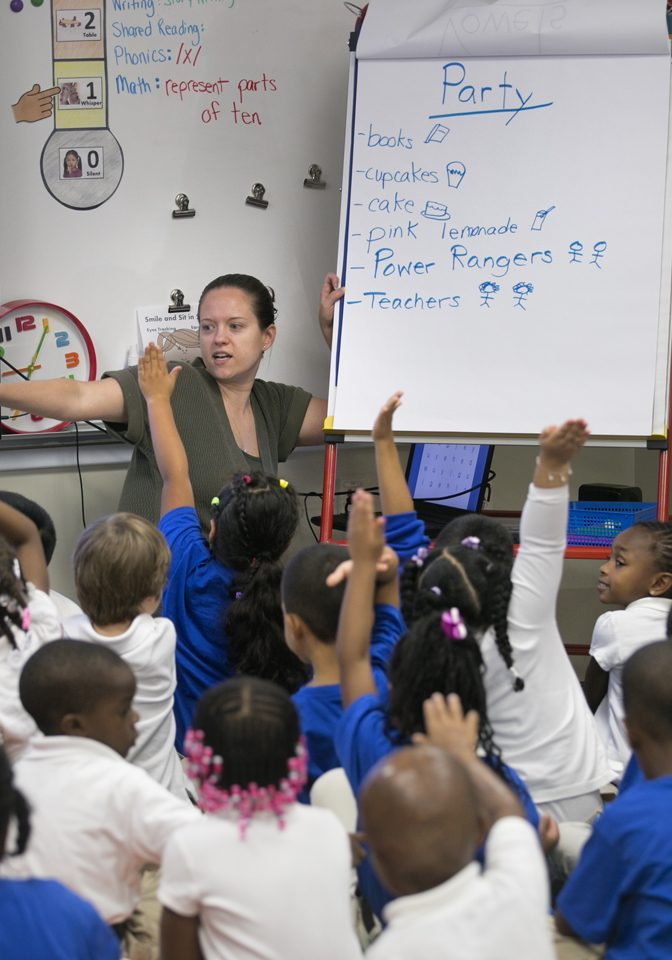The photos shows a primary school teacher with students eager to answer her question.