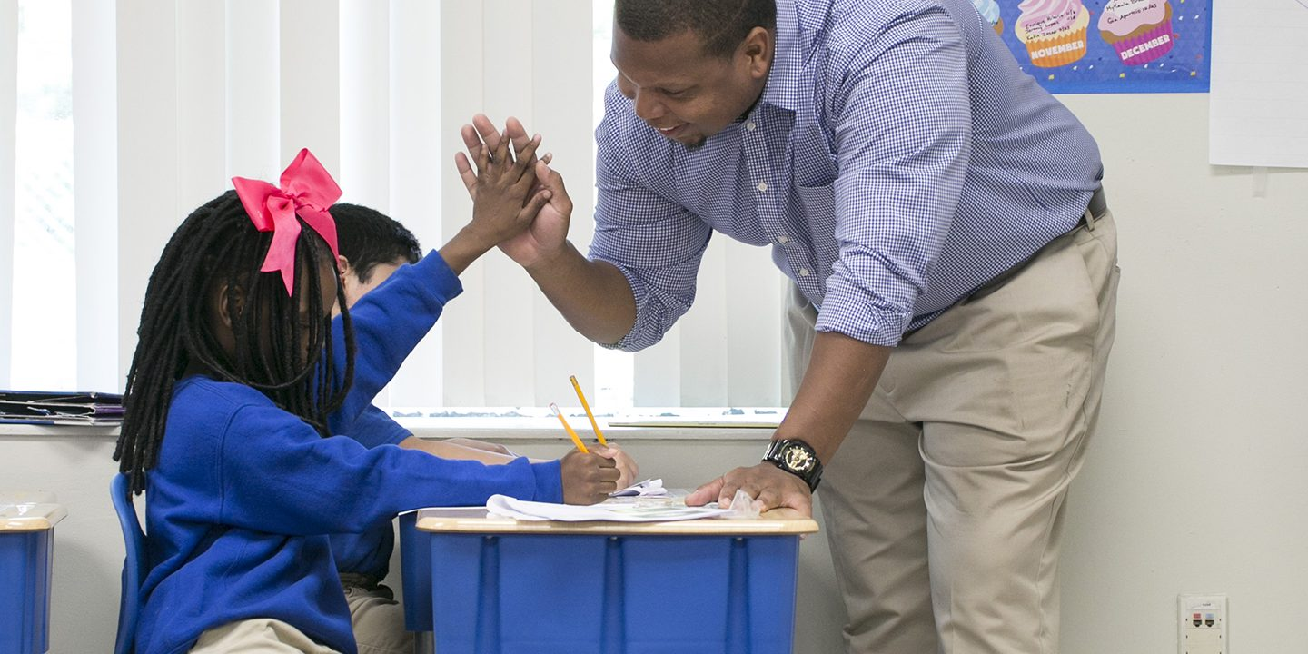 The photo shows a primary school teacher high-fiving a student for giving the correct answer.